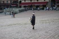 signora che getta pane bagnato ai piccioni piazza del campo (3)